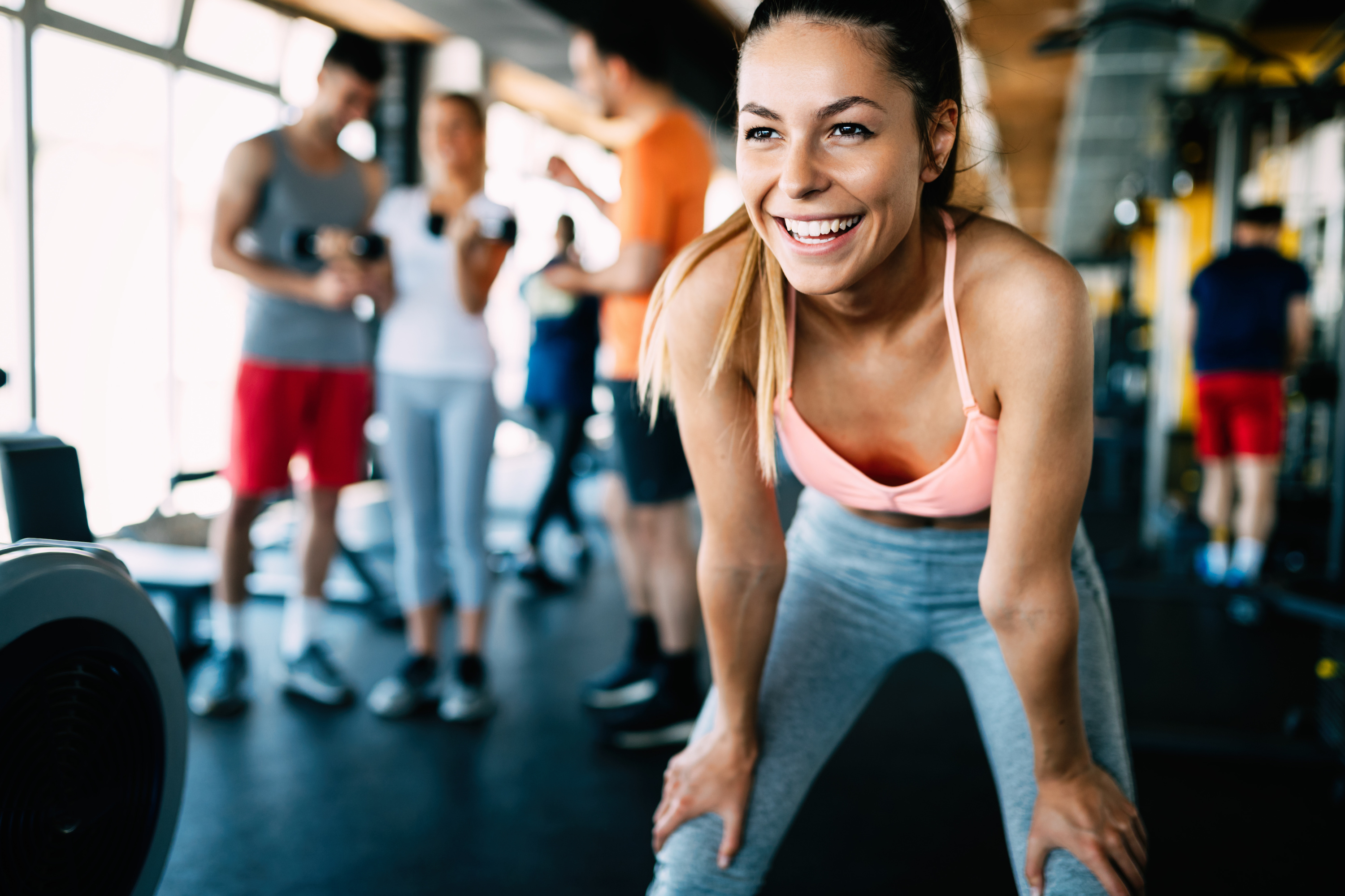 Close up image of smiling attractive fit woman in gym